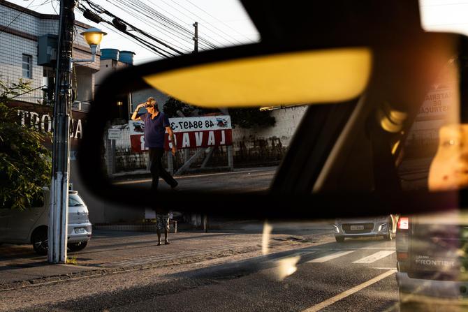 Foto horizontal colorida tirada de dentro de um carro em uma via pública, iluminada por um sol próximo do horizonte.  Em destaque, ocupando quase toda a foto, está a imagem refletida no retrovisor interno do veículo: um homem caminhando na direção do sol com a mão erguida na altura das sobrancelhas para proteger os olhos da luz forte.