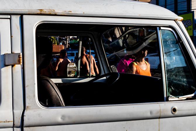 Foto vertical colorida. O observador está ao lado de uma Kombi, próximo da janela do passageiro olhando para dentro do veículo. A foto está emoldurada por parte da área externa da porta, com o vidro abaixado. A lataria apresenta amassados, pontos de ferrugem e um buraco indica o local onde deveria estar o retrovisor. Dentro do carro pouco se percebe além de um pedaço do banco marrom e do volante. Pessoas, veículos e partes de uma paisagem urbana são percebidos através do vidro dianteiro e da janela do motorista, que está com o vidro abaixado.