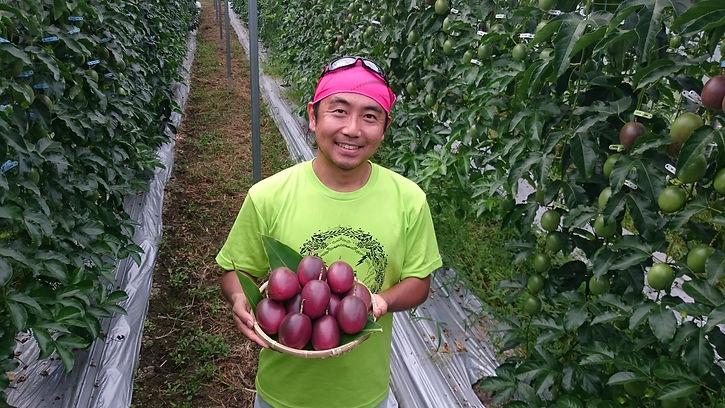 パッションフルーツを持つくっかるのうえん農園代表岩田聡