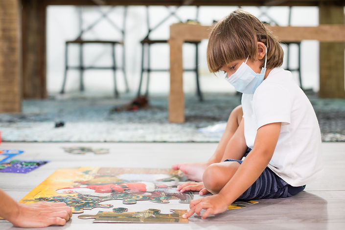 Child with a mask doing puzzle