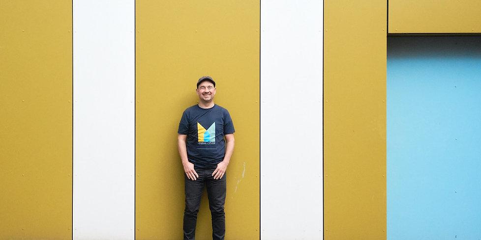 Der Künstler Guido Klumpe steht lächelnd vor einer farbigen Wand