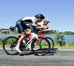Triathletes on triathlon bikes in sunshine and TeamAllOut triathlon suits