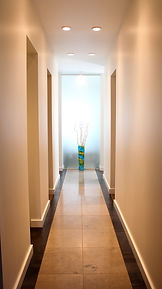 Long hallway with tile floors and a vase