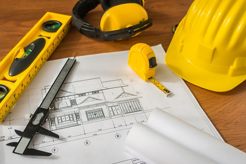 construction-plans-with-yellow-helmet-drawing-tools-bluep.jpg