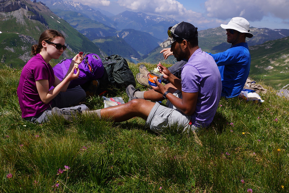 Three hikers having a picnic over the Alps' mountain range