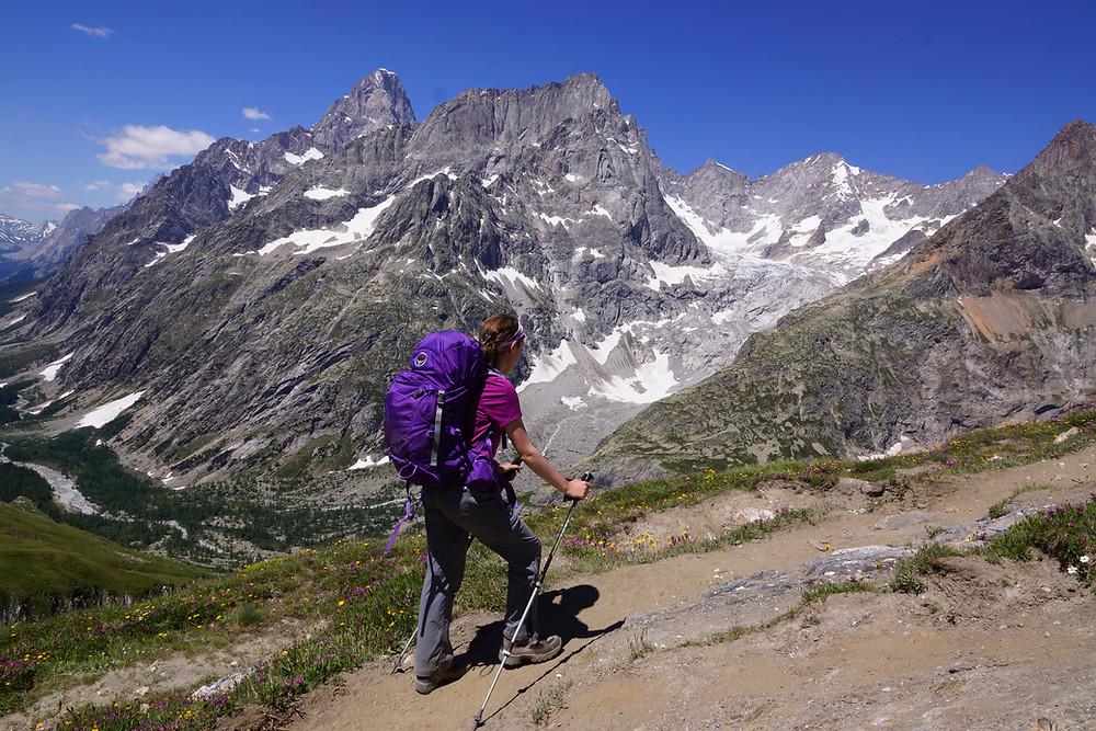 Female hiker walking uphill in front of alpine scenery