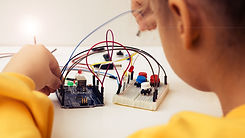 A cute girl constructs robot arduino and program it. The boards and microcontrollers are o