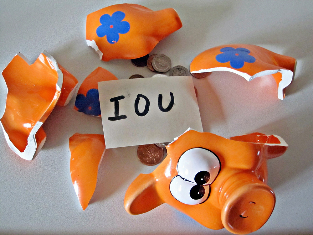 A broken piggy bank, with IOU written out on a piece of paper among a few remaining coins.