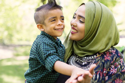 A mother wearing a hijab holding her son and smiling