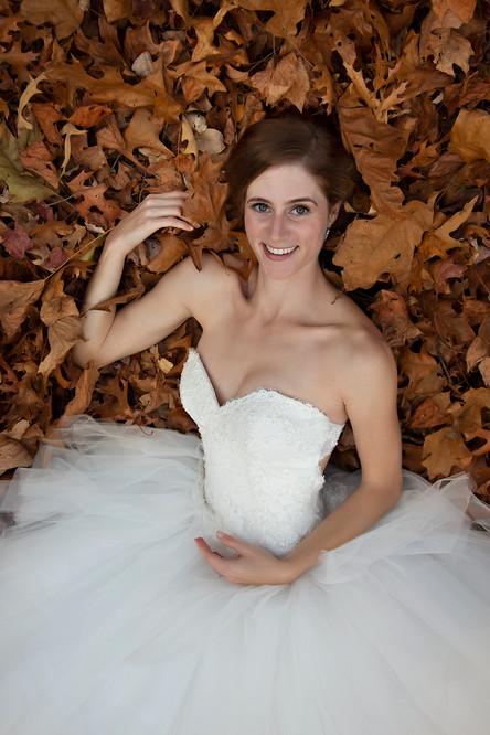 Bride laying in leaves.jpg