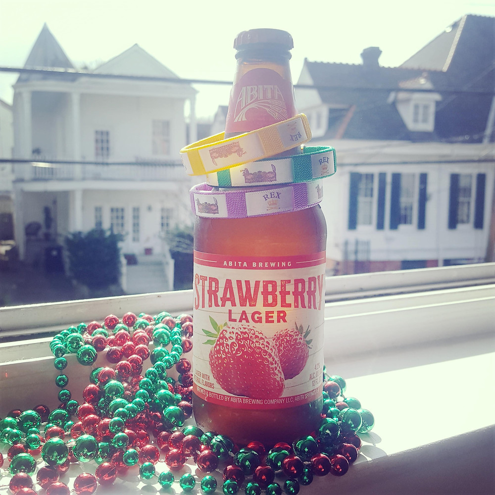 Bottle of beer on a window sill with Mardi Gras beads