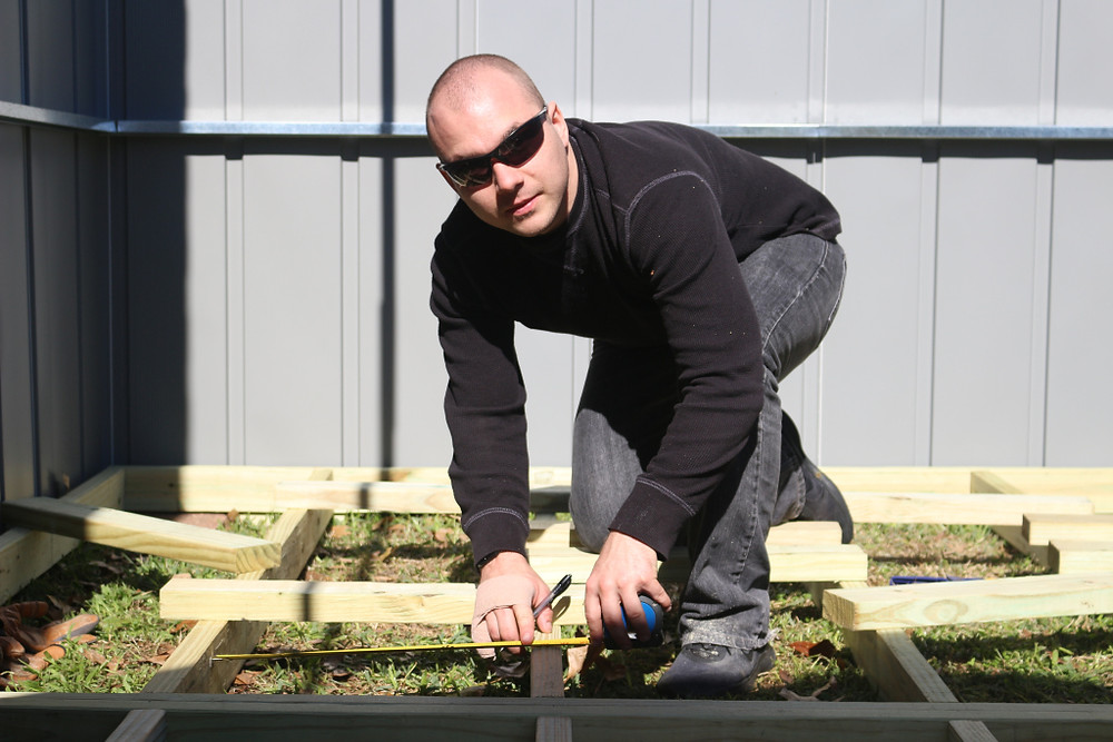 man building the floor of a shed