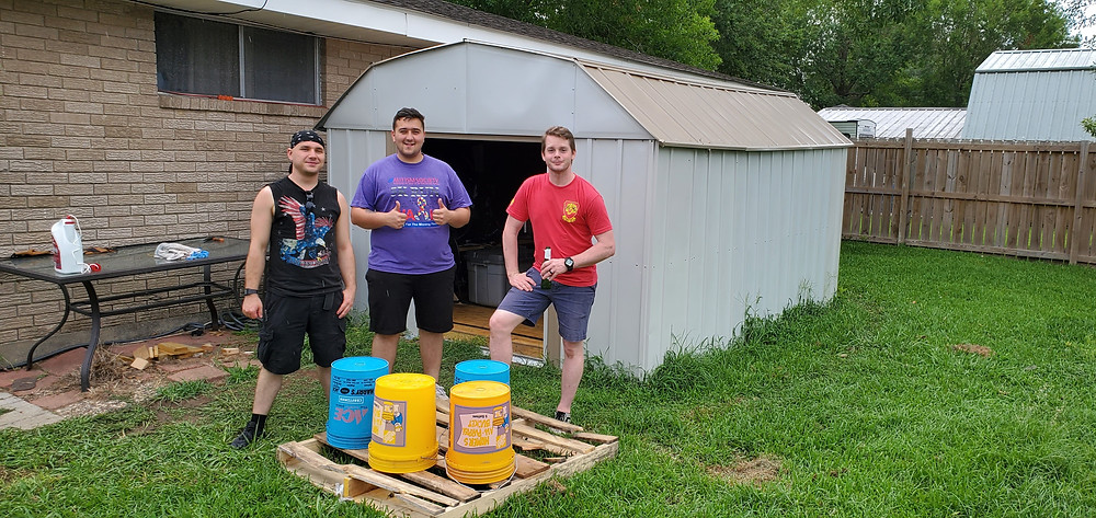 three guys standing in front of a shed