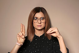 Woman using sign language on color backg