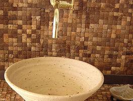 Отделана стена и столешница кокосовой мозайкой в санузле.