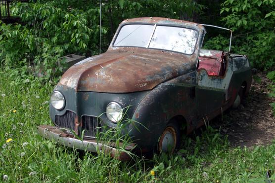 Old blue car in junk yard left side 08.j