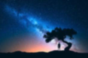 image de la voie lactée avec un homme de dos entrain de la regarder