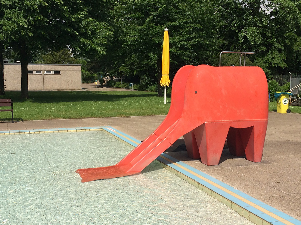 Eine Rutsche in Form eines roten Elefanten, die an einem Kinderschwimmbecken steht