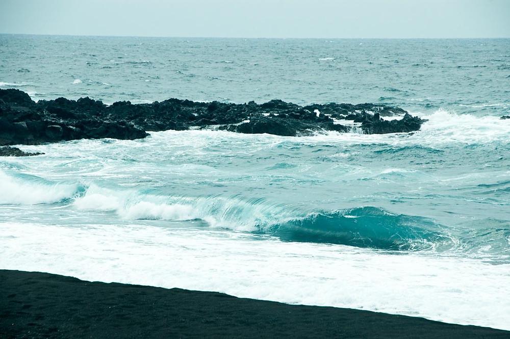 Die Wellen des pazifischen Ozeans branden auf den schwarzen Sand des Strandes