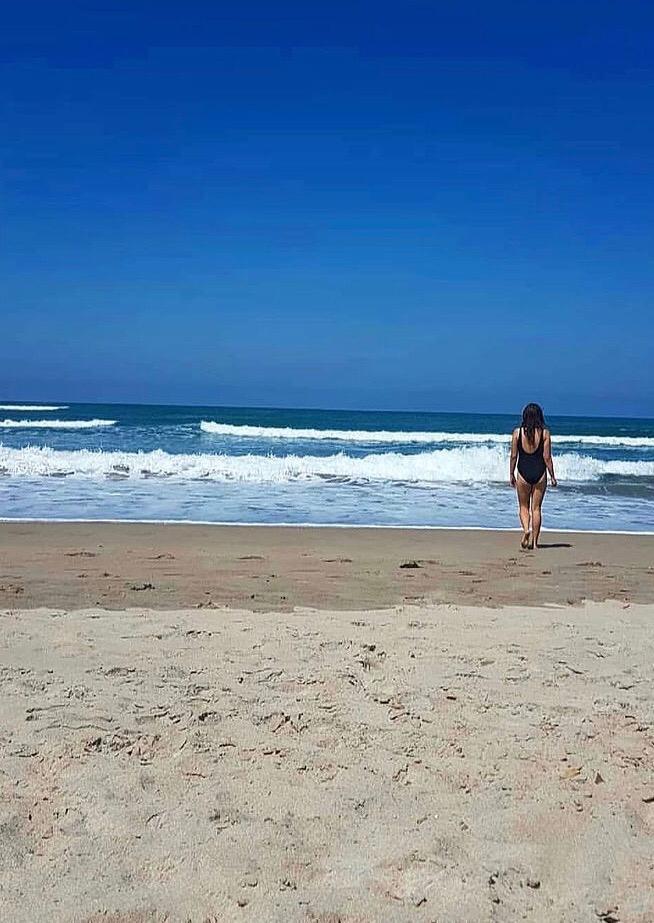 Badegast Leonie geht ins Meer, vor ihr brechen die Wellen