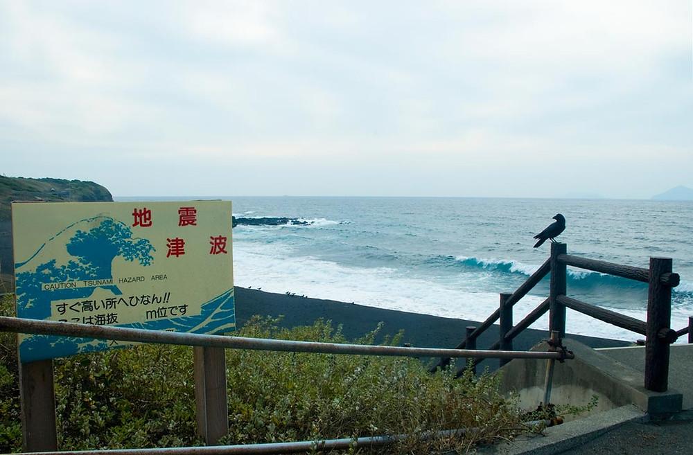 Auf einem Schild oberhalb des Strandes wird auf die Gefahr eines Tsunamis in japanischer Schrift hingewiesen. Auf dem Treppengeländer sitzt ein einzelner Rabe