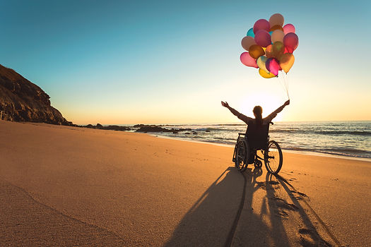 Handicapped man on a wheelchair with colored balloons at the beach_edited.jpg