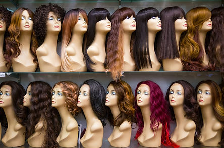a row of mannequins on a shelf in a wig