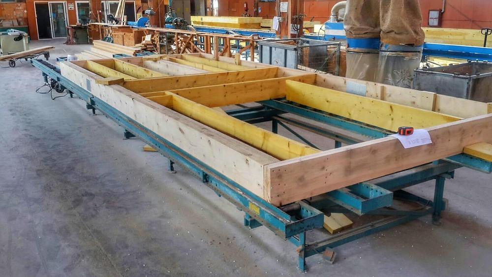 Casele pe structură timberframe se fabrică în hală. Panourile prefabricate se debitează pe bancul de lucru cu toleranțe de câțiva mm.