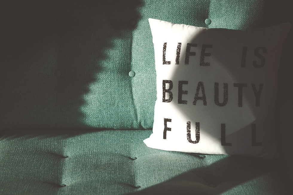 a green sofa with a white pillow that reads life is beauty full