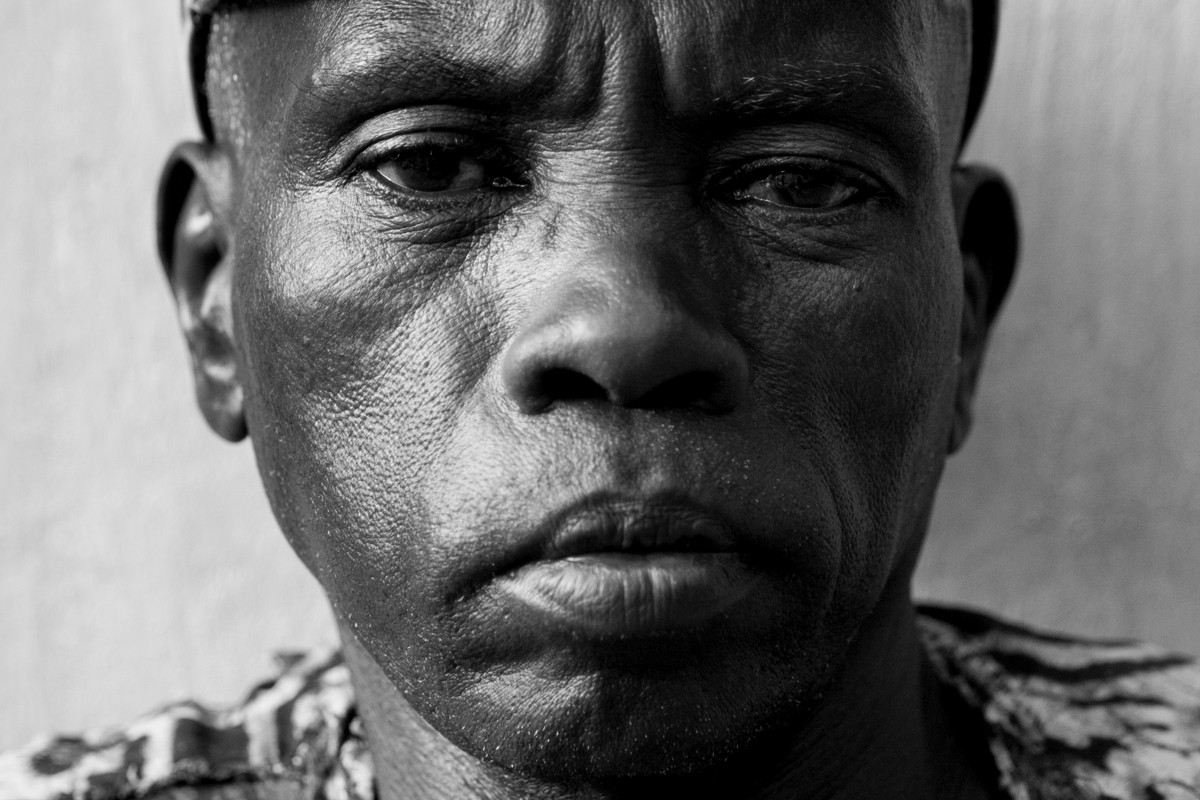 """Sagin Dennis Baldin - """"They say they are looking for witches - how can I just look at you and say you are a witch? What is witch? You don't know what is a witch..."""" .  Sagin Denis Baldin formerly lived in Sintet village that was targeted by the former Gambian President Yahya Jammeh in a witch hunt. """"My mom, my father, uncles, aunts, they were all arrested and taken...they gave them a special medicine to drink, I don't know what type of medicine is that. They were flat down, they drink and they were flat down. Some lay there for 3 days or 4 days.They will force you to say that you are a witch - so many people are dead in our village. (Previously) Anything they say they will pick you up, arrest.To arrest someone is just like dinking water, it's easy for them.Nobody's safe...anything you said they'll take you. Even when you are talking you use a tone and see who is passing because everyone was under threat. If you say, you are in trouble - somebody else go and report you, you'll be taken.Everybody was afraid before these changes come (Jammeh leaving), everybody was afraid.This former government really disturbed the Gambians.A lot of people are dead, some are lost""""  Mr. Baldin left his village for safety reasons but was followed and beaten by military officers one night close to his current home. To this day, he does not feel safe walking the streets."""