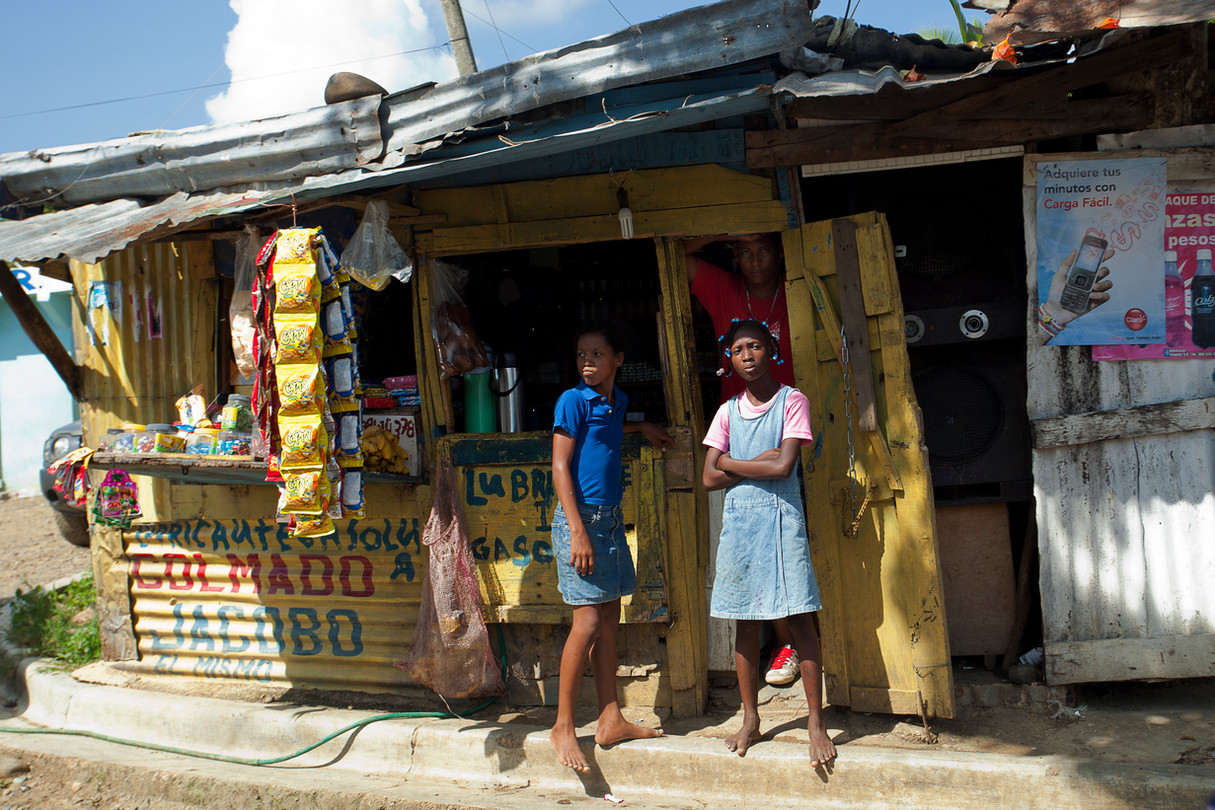 A group hangs around outside a colmado in a slum not far from the capital in the DR