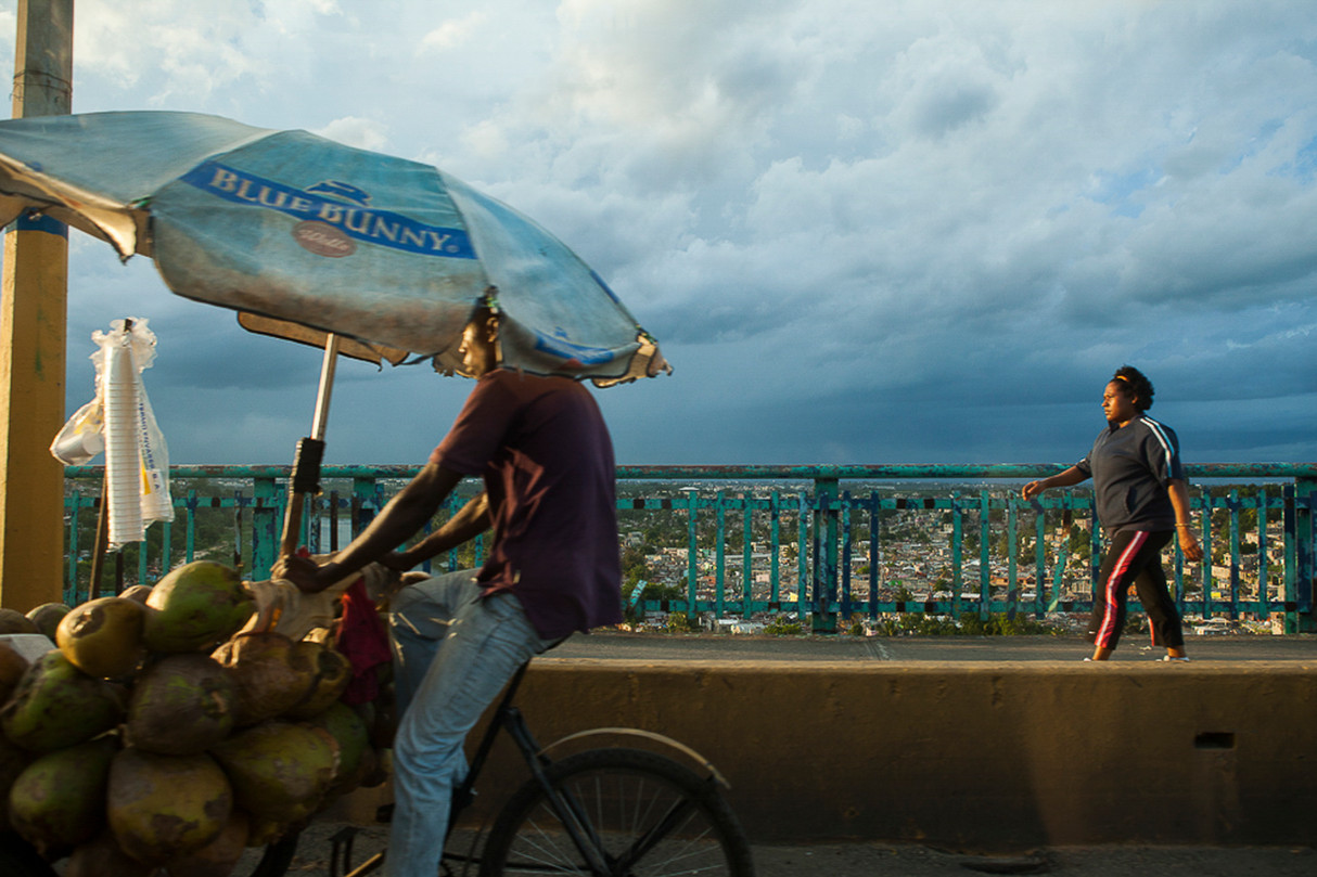 A man bicycling with coconuts and a woman walking along the highway in Santo Domingo, DR