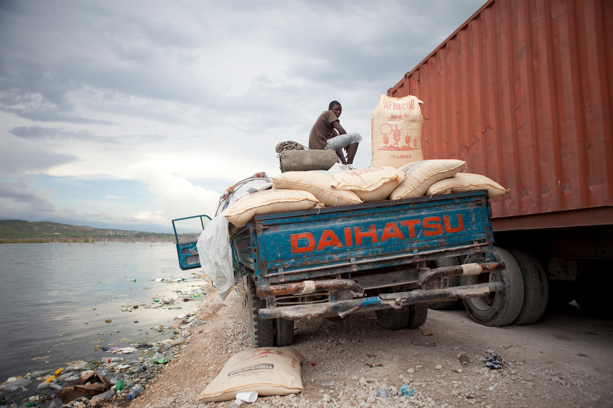A Haitian man sits on top of a truck delivering wheat at the border market between Haiti and the Dominican Repubic.  The flooding of Lake Sumatra can be seen to the left and has threatened the road the man sits on