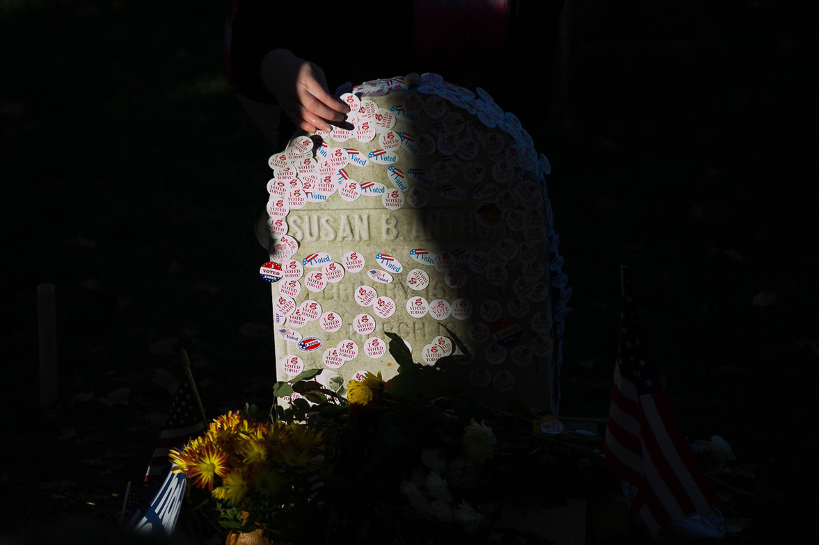 """A woman places an """"I voted"""" sticker on the gravesite of the suffragist Susan B. Anthony on election day between Hillary Clinton and Donald Trump"""