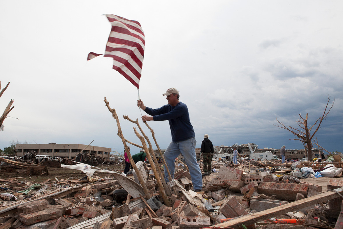 A man plants an American flag amongst the rubble in the aftermath of tornado in Moore, OK