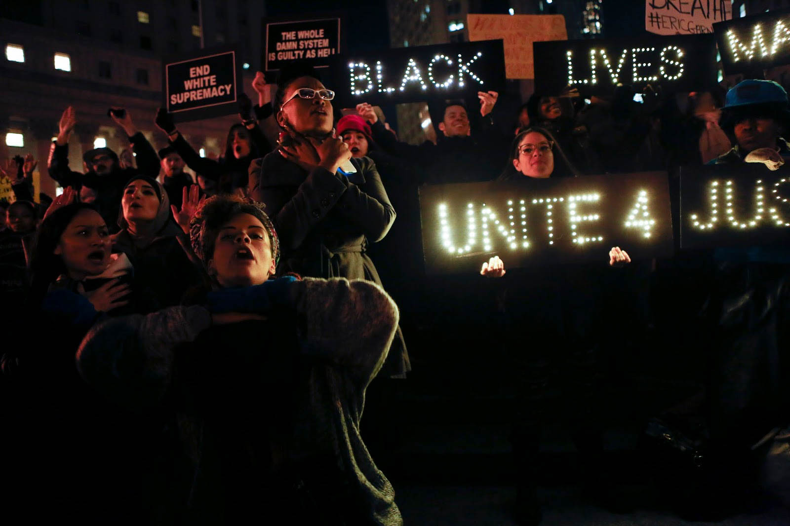 "Protestors hold their throats and chant ""I can't breathe"" in a protest of the killing of Eric Garner in New York City"