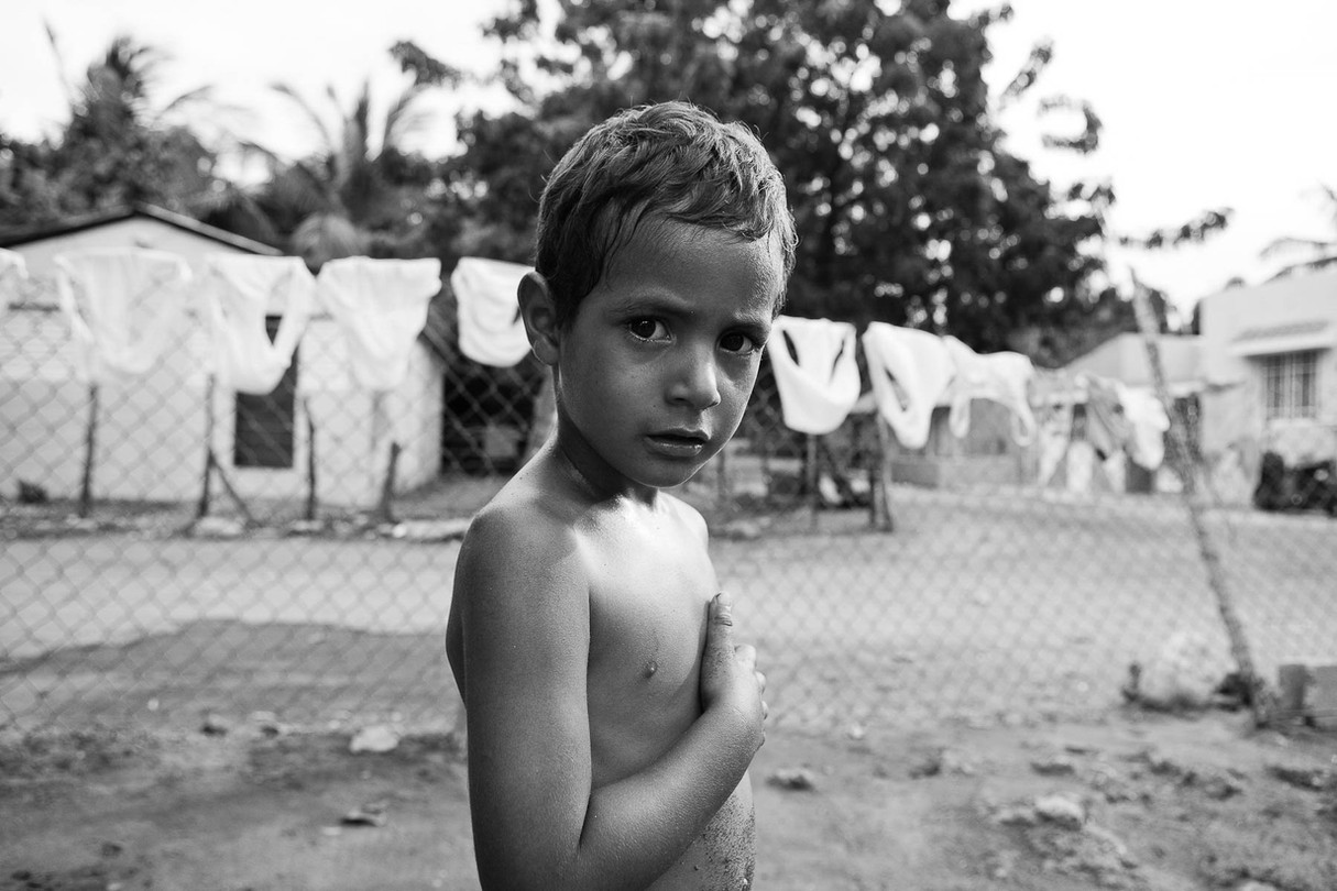 Angel, age 3, in his front yard looks with curiosty in Salinas, DR