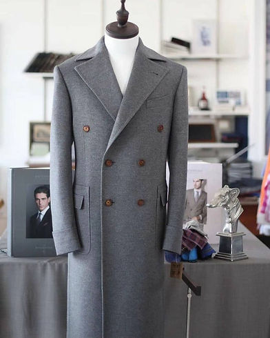 Gray, custom-tailored, double-breasted overcoat with brown buttons.