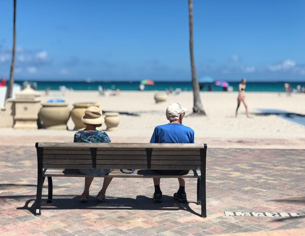 adult beach bench couple depth of field focus leisure miami ocean recreation relaxation rest retired retirement sea seashore sit sitting summer vacation wooden bench