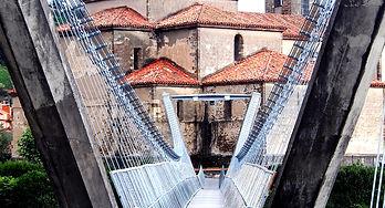 Cangas del Narcea - El Puente Colgante, con la Basílica de La Magdalena al fondo