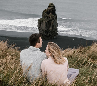 couple-sitting-in-grass-on-black-sand-be