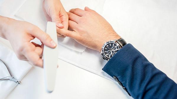 Man gets his manicure done, hands closeu