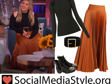 Kelly Clarkson's black cold shoulder sweater, belt, orange pleated skirt, and studded boots