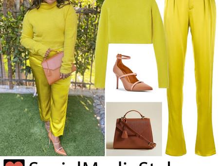 Mindy Kaling's yellow turtleneck and satin pants and brown bag and heels