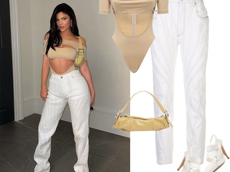 Kylie Jenner's cutout nude bodysuit, white pants, yellow bag, and white heels