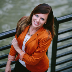 Headshot of long, brown haired woman in a burnt orange blazer next to a metal fence and river in Durham, NC