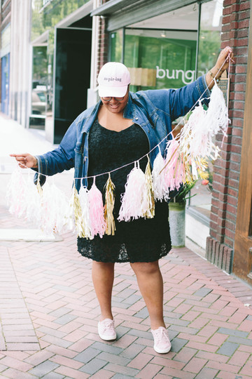 Branding photography for black woman wearing pink hat and holding pink and gold tinsel for the Aspiring Co brand in Durham, NC