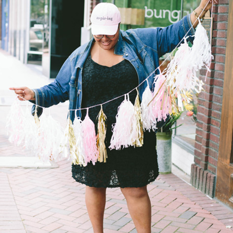 Headshot of black woman with a pink hat, black dress, and jean jacket holding pink and gold tinsel in downtown Durham, NC