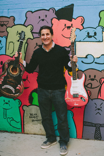 Brand photography of a man holding two guitars in front of a mural in Raleigh, NC