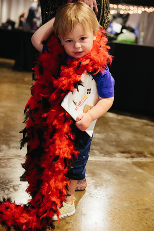 Photo of little boy wearing a feather boa at a corporate event